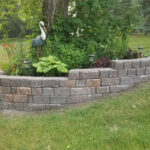 sloped retaining wall with natural boulders